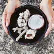 Hands holding different kinds of sea minerals (focus on corals and pebbles) — 图库照片
