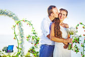 Groom kissing his bride on wedding day near floral arch on wedding venue — Stock Photo