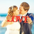 Wedding couple holding word love — Stock Photo