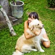Woman playing with her dog in the garden — Stock Photo