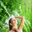 Stock Photo: Woman having shower under tropical waterfall, bali