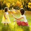 Happy young mother and her daughter blowing soap bubbles in autumn — Photo