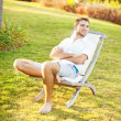 Man relaxing in summer on back yard of his house — Stock Photo