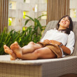 Pretty brunette womrelaxing on lounger outdoors — Stock Photo #33575975
