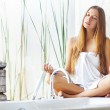 Beautiful woman wrapped with a towel relaxing in light interior — Stock Photo