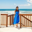 Woman in blue dress at luxury beach — Stock Photo