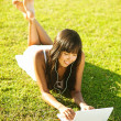 Young woman on a grass in the park or garden using laptop — Stock Photo