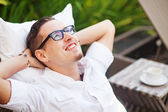 Handsome man on the outdoor bed in the garden of house — Stock Photo