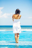 Woman in luxury resort near swimming pool - back view — Stock Photo