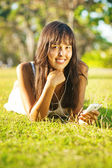 Young woman listening to music on her mobile phone or player in park — Photo