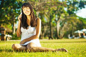 Young woman listening to music on her mobile phone in a park — Stock Photo