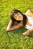 Young woman listening to music on her mobile phone or player in park — Foto Stock