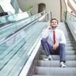 Businessman on an escalator stairs talking on mobile phone — Stock Photo
