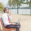 Businessman yawning on a park bench — Stock Photo