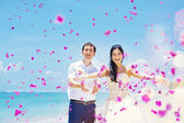 Wedding day - couple with plenty of petals — Stock Photo