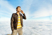Man talking on mobile phone beyond the clouds — Stock Photo
