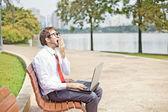 Businessman yawning on a park bench — Stock Photo