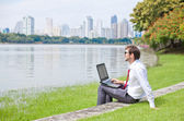 Businessman in summer park (working in green environment) — Stock Photo