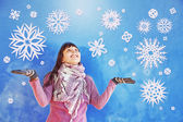 Woman catching paper snowflakes in winter — Stock Photo