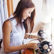Woman sewing on old sewing machine — Stock Photo #50783535