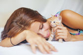 Woman on bed with cute kitten — Stock Photo