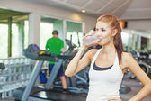 Woman drink water in gym — Stock Photo