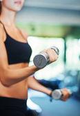 Woman in gym lifting dumbbells — Stok fotoğraf
