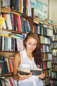 Woman reading a book in library — Stock Photo