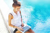 Woman working on laptop at poolside — Stock Photo