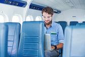 Człowiek z laptopa w samolocie — Zdjęcie stockowe