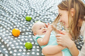 Baby snatching strand of mother's hair — Stock Photo