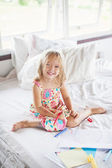 Blonde girl drawing on the bed — Stock fotografie