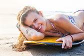 Woman lying on surfboard — Stock Photo