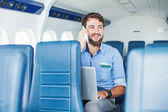 Man using phone and laptop in plane — Stock Photo