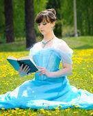 Genç kız çimlerin üzerinde kitap okuma — Stok fotoğraf