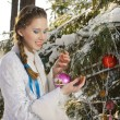 The girl decorates Christmas fir-tree — Stock Photo