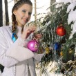The girl decorates Christmas fir-tree - Stock Photo