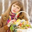 Girl holding basket with fruits and flowers — Stock Photo