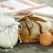 Homemade yogurt, milk, bread and eggs on a wooden table — Stock Photo