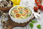 Quail eggs scrambled with nettle and cherry tomatoes — Stock Photo