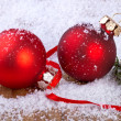 Royalty-Free Stock Photo: Red balls with snowflakes, on wooden background