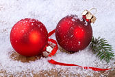 Red balls with snowflakes, on wooden background — Stock Photo