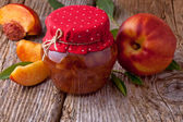 Nectarine, peach jam on wood background — Stock Photo