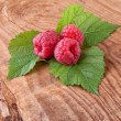 Raspberries with leaf on wooden background — Stock Photo #18123571