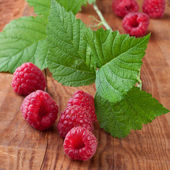 Raspberries with leafs on wooden background — Stock Photo