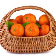 Tangerines with leaves in beautiful basket isolated on white — Stock Photo