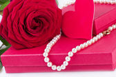Gift box with red rose and heart and pearl necklace — Stock Photo