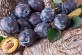 Plums with leafs on wood background — Stock Photo