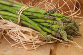 Bundle of green asparagus on wooden table — Stock Photo