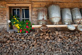 Old milk cans on a shelve at a alpine hut — Stock Photo